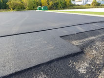 Asphalt Driveway, Parking Lot Repair. Asphalt is being put down for a driveway parking lot. Building construction and maintenance repair is an ongoing task for stock photo