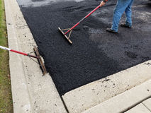 Asphalt Driveway, Parking Lot Repair. A worker is heating asphalt for a driveway parking lot. Building construction and maintenance repair is an ongoing task for royalty free stock photo