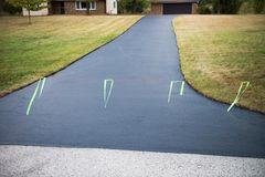 Asphalt Driveway Seal, Sealed, Sealing. Asphalt driveway after being sealed with tar. Sealing a driveway helps make it last. Keeping the surface sealed adds life Stock Image