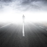 Asphalt highway perspective with walking man. In the fog Royalty Free Stock Image