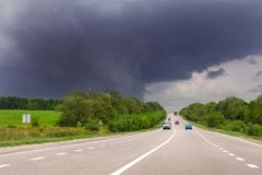 Asphalt highway road and rainy clody dark thunder sky on background. Bad stormy weather forecast. Way to hurrican Royalty Free Stock Images