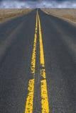 Asphalt Highway Road superior negro, nubes de tormenta en distancia Foto de archivo libre de regalías
