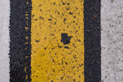 Asphalt highway texture with cracked white and yellow stripe.  Stock Photos