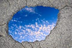 Asphalt hole and blue sky Stock Photo
