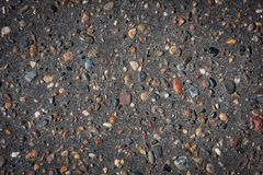 Asphalt with inlined rocks. Asphalt texture with inlined colorful rocks and small vignetting Royalty Free Stock Images