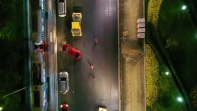 Asphalt laying at night in the city center, tram and cars passing by, top view from drone. Asphalt laying at night in the city center, tram and cars passing by stock footage