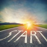 Start written to the ground on a road at sunset. Concept of new beginning and starting new opportunities. Asphalt lit by the sunset light. Road disappears in the royalty free stock images