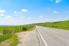 Asphalt long road crossing the green valley in a sunny summer day with bright blue sky stock images