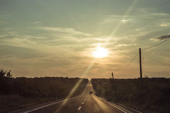 Asphalt Long Road and Vehicle Passes Through Right Lane during Golden Hour Stock Photography