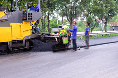 Asphalt machine paving on top of cracked road Stock Images