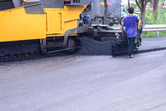 Asphalt machine paving on top of cracked road Royalty Free Stock Image
