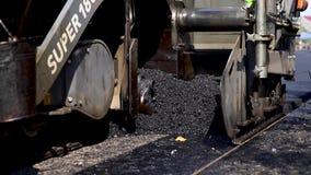 Asphalt making machine pours asphalt onto prepared road