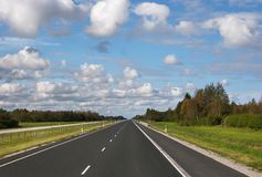 Asphalt motorway through the country side. In a sunny clear day manyclouds in the sky royalty free stock photo
