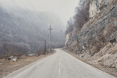 Asphalt mountain road between the rocks in the foggy gorge near the mountain river of caucazus Stock Photos