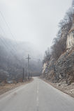Asphalt mountain road between the rocks in the foggy gorge near the mountain river of caucazus Royalty Free Stock Photography
