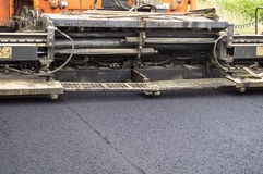Asphalt paver in action Stock Photos