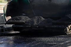 Asphalt paver machine. Closeup hot asphalt in the hopper of asphalt paver machine Stock Images