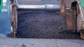 Asphalt paver machine during road construction, road construction crew apply asphalt layer stock footage