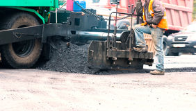 Asphalt Paving Machine. Road crew operate asphalt spreader equipment to lay down asphalt on a hot day Stock Image
