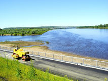 Asphalt paving machine on the river embankment Stock Photo