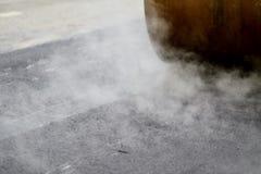 Asphalt paving with steel roller. Asphalt paving with a steel wheel roller. Steam coming out from asphalt Royalty Free Stock Photo