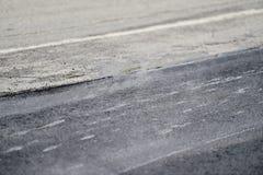 Asphalt paving with steel roller. Asphalt paving with a steel wheel roller. Steam coming out from asphalt Royalty Free Stock Image