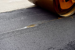 Asphalt paving with a steel wheel roller. Steam coming out from asphalt Stock Images