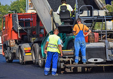 Asphalt paving vehicle at the road construction Stock Photos