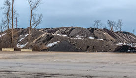 Asphalt pile. A colorful asphalt pile shot, with light snow and blue sky, and some out of place trees Royalty Free Stock Image