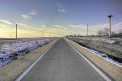 Asphalt road. Under the blue sky and the sunset in winter stock image