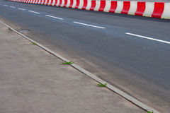 Asphalt road. With red and white color fence royalty free stock photos
