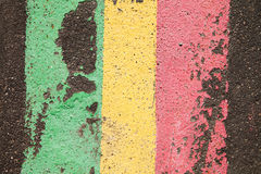 Asphalt road abstract colored lines. Green yellow red paint. Up view Stock Image