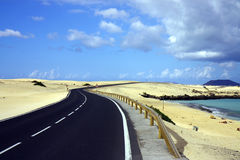 Asphalt road across desrt. Close ocean Royalty Free Stock Image