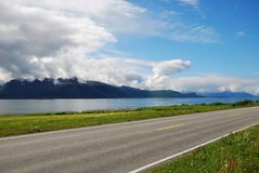 Asphalt road along the blue fjord. Stock Image