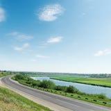 Asphalt road along river and blue sky Stock Photography