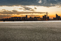 Asphalt Road And Modern City Skyline At Sunset Royalty Free Stock Photography
