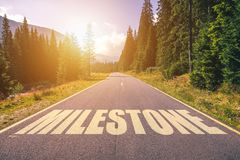 Asphalt road with arrow guideline and Milestone letters painted. On the surface. An image of a road milestones are representative of success in the future goal Royalty Free Stock Photography