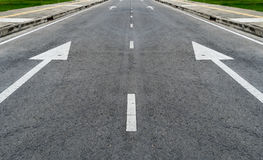Asphalt road with arrow sign Stock Photography