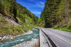 Asphalt road in Austria through the forest, valley in Austria in a beautiful summer day. Alps mountains tranquil summer view ( stock image
