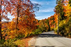 Asphalt road through autumn forest in mountains. Beautiful and colorful scenery on sunny day under the blue sky with some clouds Royalty Free Stock Image