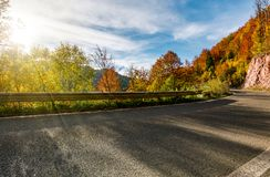 Asphalt road through autumn forest in mountains. Beautiful and colorful scenery on sunny day under the blue sky with some clouds Stock Image