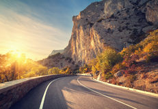 Asphalt road in autumn forest at sunrise. Crimean mountains Stock Photography