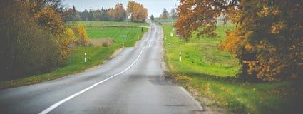 Asphalt road in autumn landscape royalty free stock image