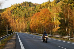 Asphalt road in the autumn landscape with a ride motorcycle, over the road forested mountain Royalty Free Stock Photo