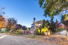 Asphalt road in the autumn street with trees and fallen leaves,. Private residential house, green fence from plants, gates, blue sky stock images