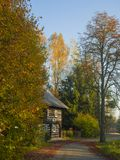 Asphalt road with autumn trees to timbered wooden cottage in gol Stock Image