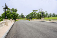 Asphalt road with balustrades and streetlamps in cloudy summer Stock Photography