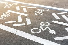Asphalt road with bicycle and electric transport lane. Cycle and zero emission vehicles white sign on floor. Recreation. Area for green energy transport in city royalty free stock image