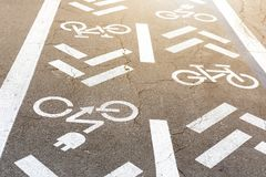 Asphalt road with bicycle and electric transport lane. Cycle and zero emission vehicles white sign on floor. Recreation area for. Green energy transport in city royalty free stock images