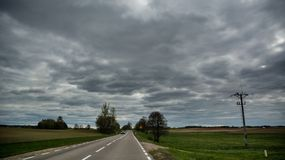 Asphalt road with car far away on overcast spring day. With electricity pole, in Lithuania Stock Photo